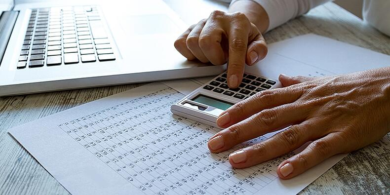 person using calculator at work station