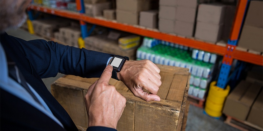 person checking their smart watch in warehouse