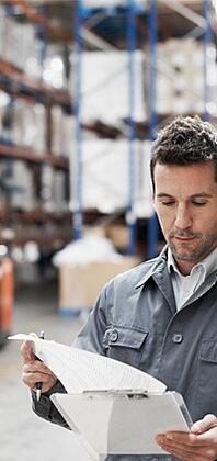 man consulting clipboard in warehouse